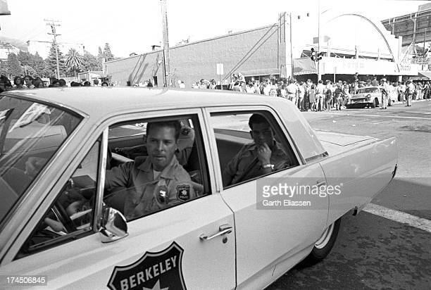 Police officers patrol Telegraph Avenue in a cruiser during the Fourth of July street celebrations Berkeley California July 4 1969