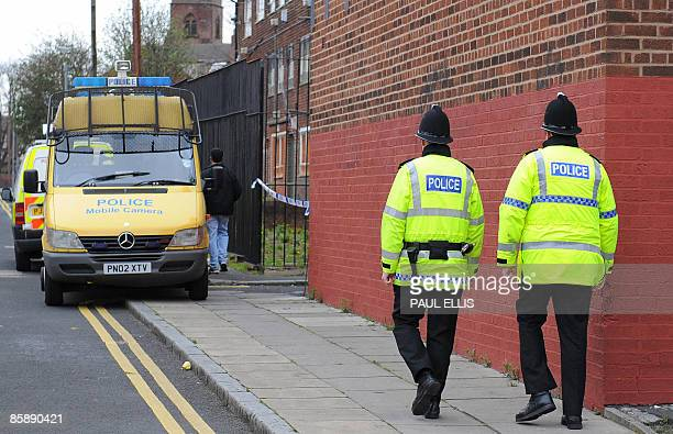 Police officers patrol the area around a house in Liverpool north west England on April 10 2009 following arrests and raids in Liverpool Manchester...
