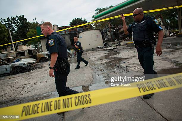 Police officers patrol the BP gas station following a shooting death by police August 15, 2016 in Milwaukee, Wisconsin. Hundreds of angry people...