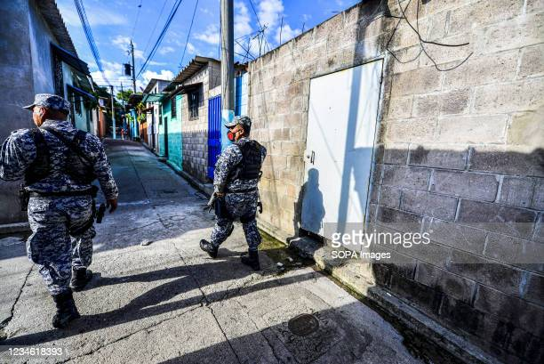 Police officers patrol the community during a search operation for gang members. El Salvador's National Police performs police operations at the...