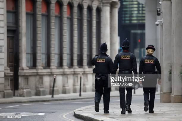 Police officers patrol the near-deserted streets of the City of london on April 16 during the novel coronavirus Covid-19 pandemic. - The British...