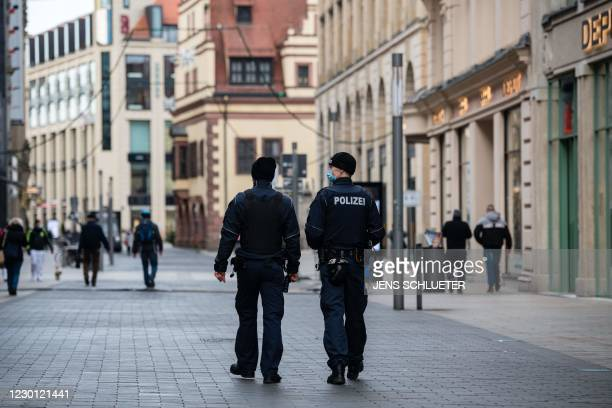 Police officers patrol through the almost deserted shopping streets in the city center in Leipzig, eastern Germany on December 14, 2020 amidst the...