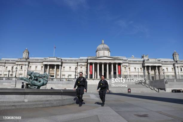 Police officers patrol Trafalgar Square in view of the National Portrait Gallery in London, U.K., on Tuesday, March 24, 2020. The U.K. Is in lockdown...