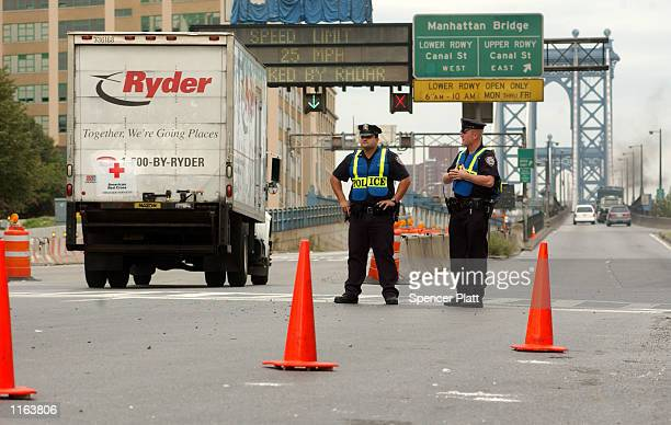 Police officers patrol traffic as vehicles enter the Manhattan Bridge from the Brooklyn borough September 27, 2001 in New York City. New York Mayor...