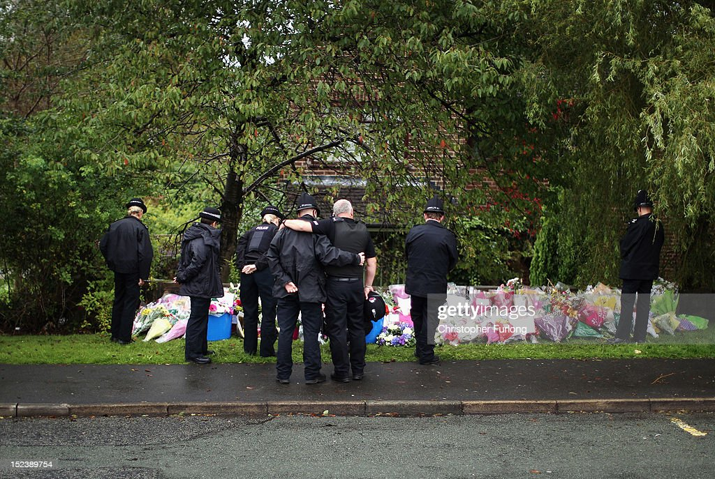 Police officers pause for thought after laying flowers near to the scene of the shooting of WPCs Nicola Hughes and Fiona Bone in Hattersley on September 20, 2012 in Manchester, England. Local man Dale Cregan, 29, has been arrested in connection with the shooting of WPCs Nicola Hughes and Fiona Bone, who suffered fatal injuries in a gun and grenade attack in Mottram, during a routine call to investigate a burglary in Abbey Gardens on Tuesday.