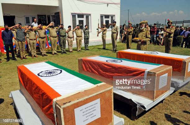 A senior officer pays respect to colleagues who were killed by militants during a wreath laying ceremony at a base camp Shopian on September 21 2018...