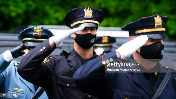 Police officers pay their respects during the funeral of Glen Ridge Police Officer Charles Roberts after he passed away from the coronavirus on May...