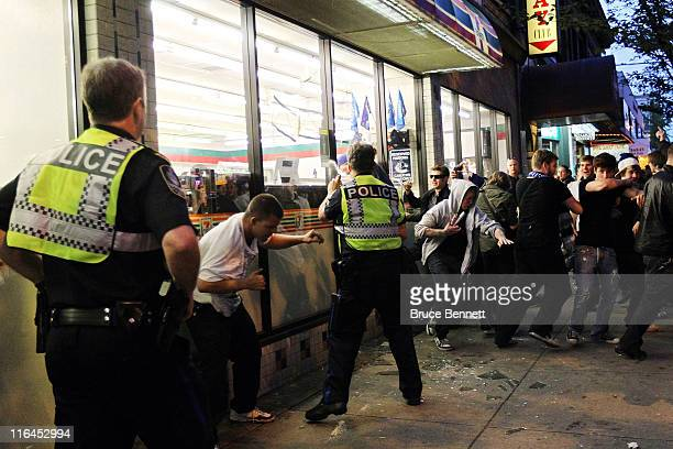 Police officers pepper spray a group of rioters trying to break into a 711 on June 15 2011 in Vancouver Canada Vancouver broke out in riots after...