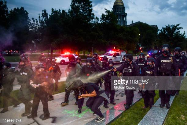 Police officers pepper spray a woman next to the Colorado State Capitol as protests against the death of George Floyd continue for a third night on...