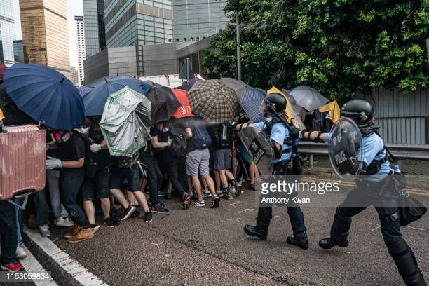 Police officers pepper spray during a clash with antiextradition protesters outside the Legislative Council Complex ahead of the annual flag raising...