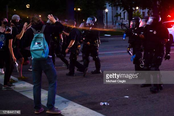 Police officers pepper spray people next to the Colorado State Capitol as protests against the death of George Floyd continue for a third night on...