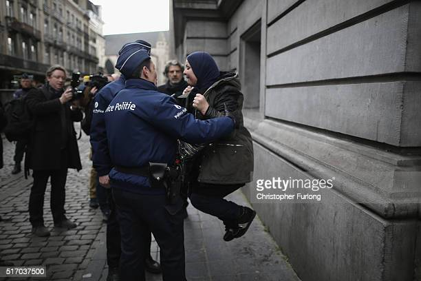 police officers placate a woman as emotions run high after people observed a one minute silence at the Place De La Bourse in honour of the victims of...