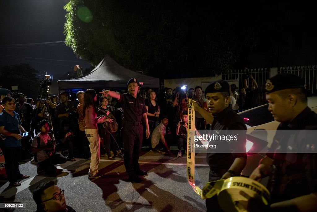 Police officers place caution tape outside the residence of Najib Razak, Malaysia's former prime minister, in Kuala Lumpur, Malaysia, on Thursday, May 17, 2018. Malaysia's Prime Minister Mahathir Mohamad said he wouldn't cut a deal with Najib if any wrongdoing was found in a corruption probe into state fund 1MDB. Najib has repeatedly denied wrongdoing after 2015 revelations that around $700 million -- alleged to be 1MDB funds -- appeared in his personal accounts before the prior election in 2013. Photographer: Sanjit Das/Bloomberg via Getty Images