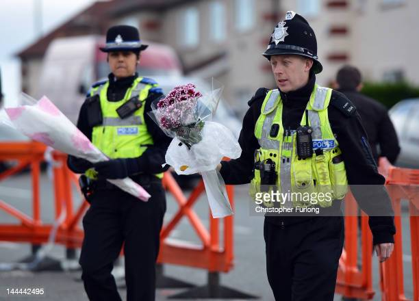Police officers place flowers on the pavement outside a house in Allenton where a fire claimed the lives of six children on May 14 2012 in Derby...