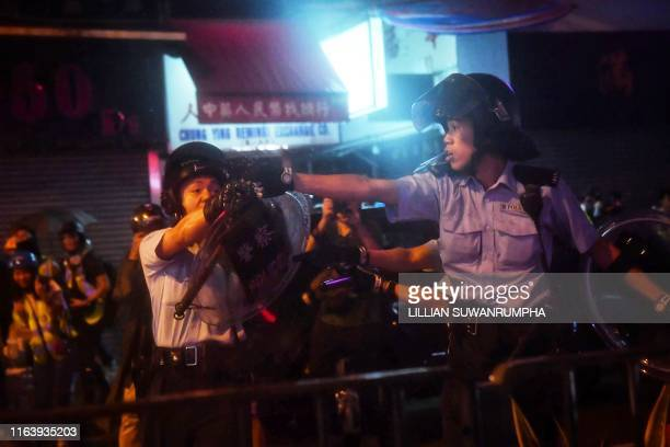 TOPSHOT Police officers point their guns at protesters in Tseun Wan in Hong Kong on August 25 2019 in the latest opposition protests to a planned...