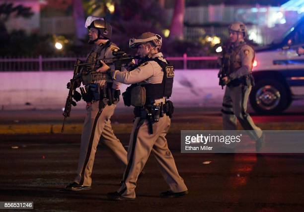 Police officers point their weapons at a car driving down closed Tropicana Ave near Las Vegas Boulevard after a reported mass shooting at a country...
