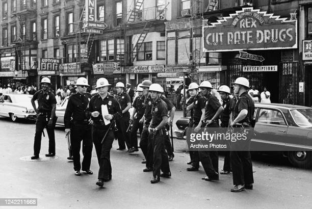 Police officers prepare to disperse the protestors on Lenox Avenue, between 127th and 128th Street in Harlem, New York City, 23rd July 1964. The...