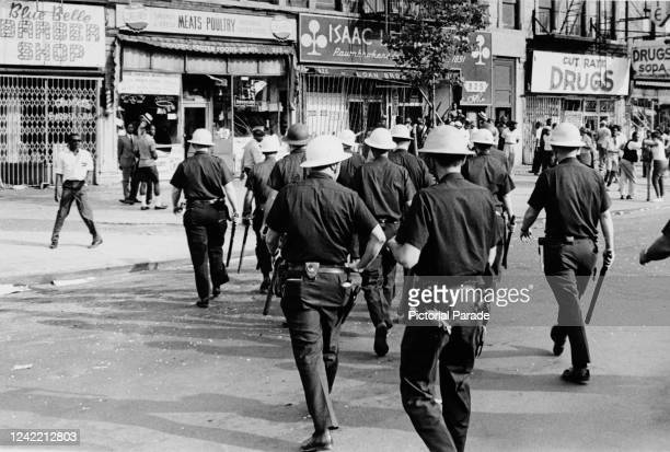 Police officers prepare to disperse the protestors on Lenox Avenue, between 127th and 128th Street in Harlem, New York City, July 1964. The protests...