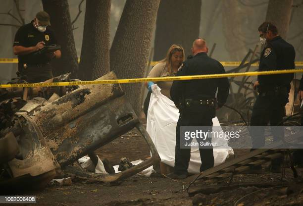 Police officers prepare to remove human remains that were found in a car that was destroyed by the Camp Fire on November 15 2018 in Paradise...