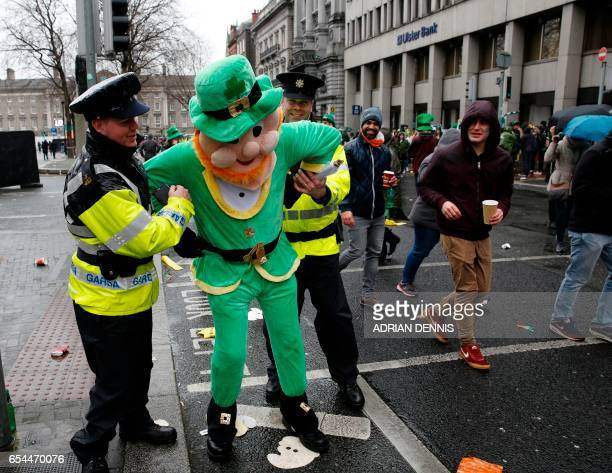 Police officers pretend to arrest a man dressed in a leprechaun outfit as he poses for a photograph along the parade route during the St Patrick's...