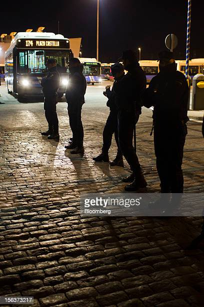 Police officers protect buses as they leave the Empresa Municipal de Transportes de Madrid depot on the morning of a general strike in Madrid Spain...
