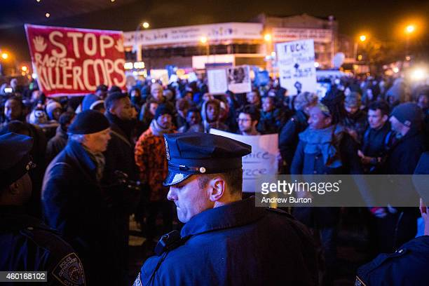 Police officers protect people entering the Barclays Center for a Brooklyn Nets game while demonstrators protest a Staten Island New York grand...