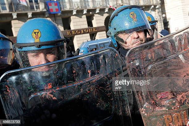 Police officers protect themselves with their shields as protesters throw paint bombs during a protest by students against the local government in...