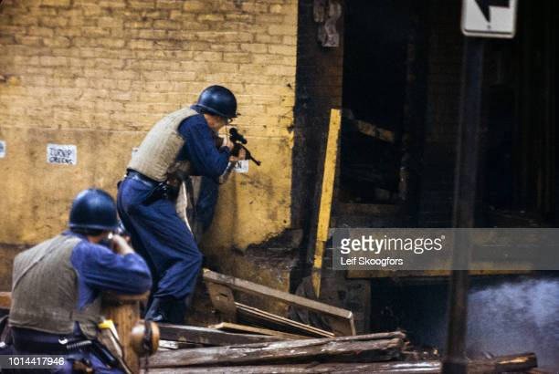 Police officers provide cover as a water is directed at the MOVE house during a shootout with the Black Power commune, Philadelphia, Pennsylvania,...