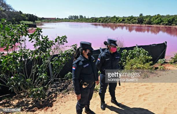 Police officers provide security to locals protesting on the shore of the Cerro Lake, formed from a meander of the Paraguay River, against a nearby...