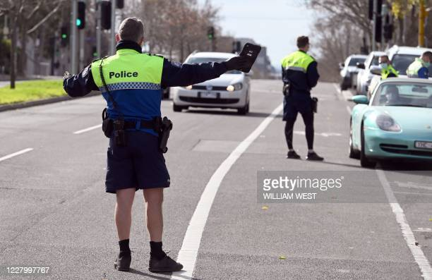 Police officers pull a car over for a licence and permit check in Melbourne on August 11 during a strict stage four lockdown of the city due to a...