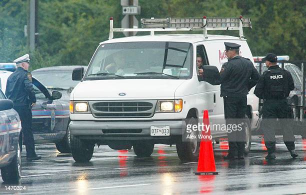 Police officers pull over and question the occupants of a van which matches the description of a suspected vehicle at a checkpoint on Route 1 October...