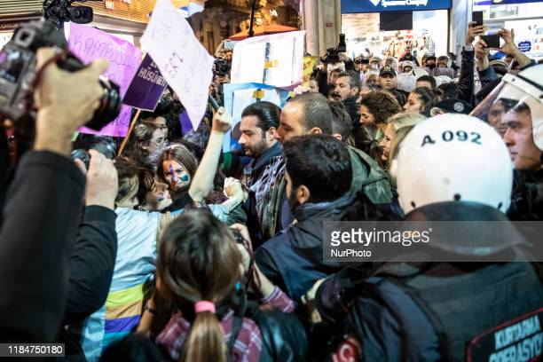 Police officers push a small group of demonstrators during the International Day for the Elimination of Violence against Women rally at Beyoglu...
