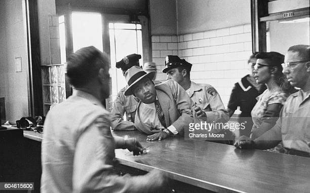 Police officers push American religious and Civil Rights leader Dr Martin Luther King Jr across a police desk as he is booked for loitering...