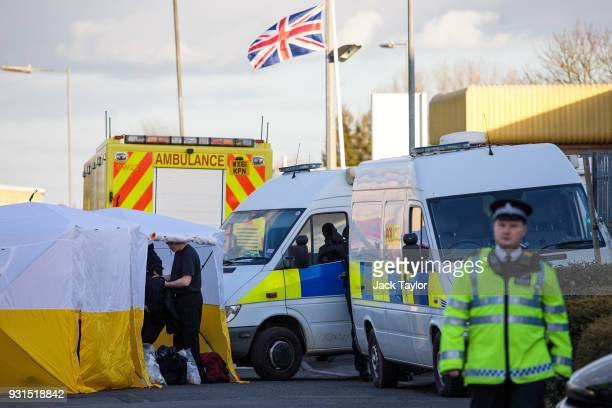 Police officers put on protective clothing in a tent outside a vehicle recovery centre as investigations continue into the poisoning of Sergei...