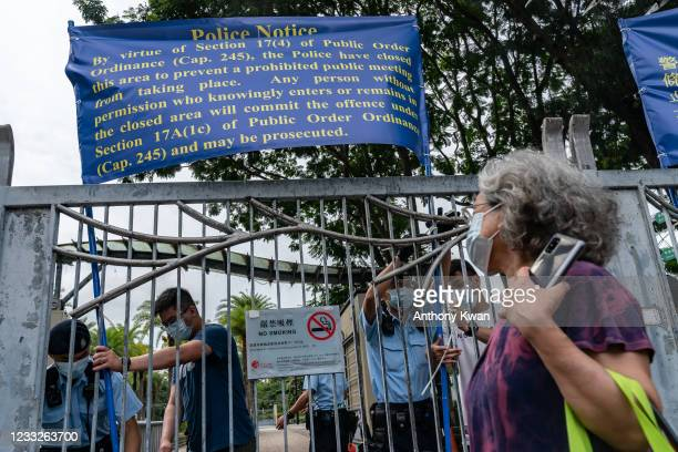 Police officers put up notices as they patrol Victoria Park, after closing a venue where Hong Kong people traditionally gather annually to mourn the...
