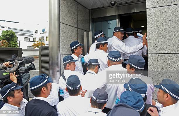 Police officers raid the headquarters of the 'yakuza' crime syndicate the 'Yamakengumi' in Kobe Hyogo prefecture in western Japan on September 9 2015...