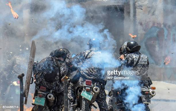 Police officers react after an explosive device exploded as they rode past during a protest against the elections for a Constituent Assembly in...