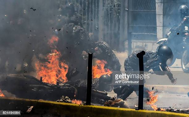 TOPSHOT Police officers react after an explosive device exploded as they rode past during a protest against the elections for a Constituent Assembly...