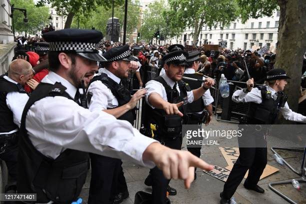 Police officers react after protestors pushed through barriers near the entrance to Downing Street during an antiracism demonstration in London on...
