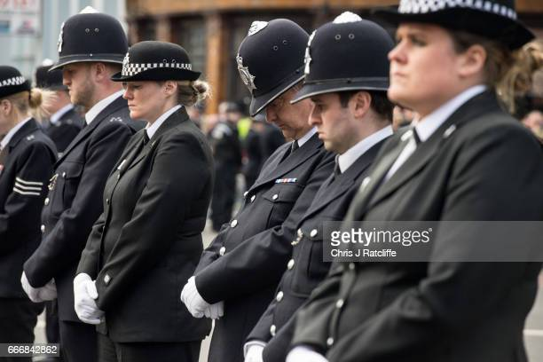 Police officers react as a hearse carrying the coffin of PC Keith Palmer makes its way down Southwark Street past lines of police officers after his...