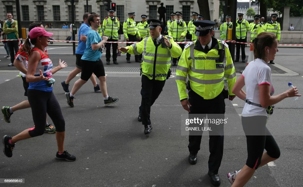 Police officers react as they attempt to cross a road through the path of runners during the the Vitality London 10km run in central London, on May 29, 2017. Operation Temperer, which involved the deployment of armed troops on patrol alongside police, will be wound down on Monday night, at the end of the holiday weekend. Prime Minister Theresa May lowered the terror threat level, which had been hiked following the May 22 attack at Manchester Arena. / AFP PHOTO / Daniel Leal-Olivas