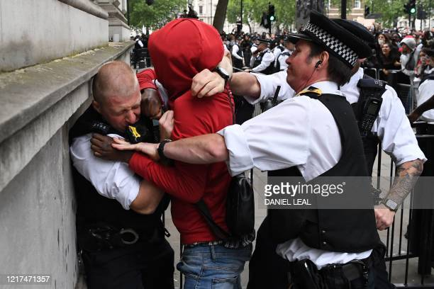 Police officers react as they attempt to detain a protestor near the entrance to Downing Street during an antiracism demonstration in London on June...