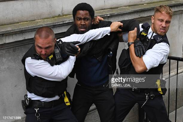 TOPSHOT Police officers react as they attempt to detain a protestor near the entrance to Downing Street during an antiracism demonstration in London...