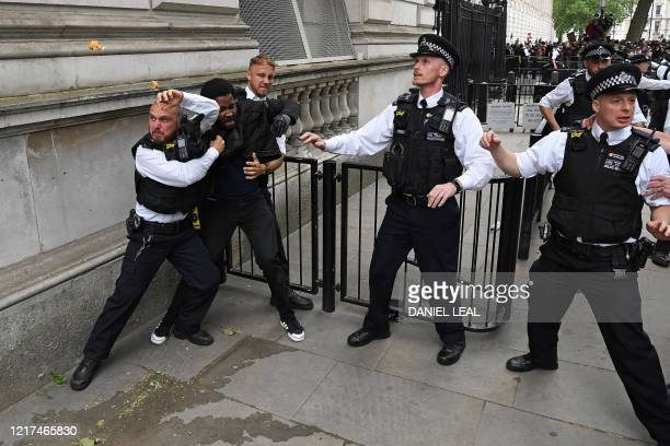 Police officers react to an orange peel being thrown at them as they scuffle with a protestor near the entrance to Downing Street during an...