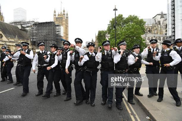 Police officers reacts as they are goaded by protesters near the The Houses of Parliament, during an anti-racism demonstration in London, on June 3...