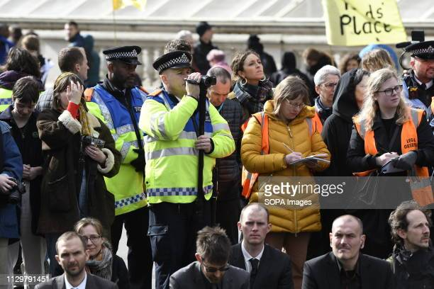 Police officers recording Extinction Rebellion activists outside Downing Street Hundreds of activists from the Extinction Rebellion climate change...