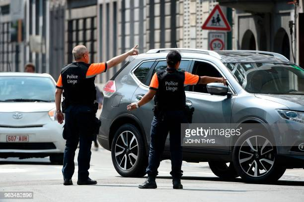 Police officers redirect traffic in the eastern Belgian city of Liege on May 29 near the site where a gunman killed two female police officers and a...