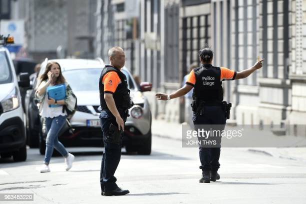 Police officers redirect traffic in the eastern Belgian city of Liege on May 29 near the site where an armed man shot and killed police officers...
