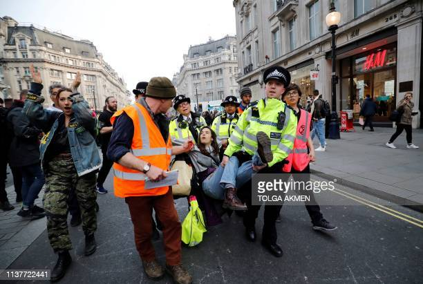 Police officers remove a climate change activist at Oxford Circus on the third day of its blockade by environmental protest group Extinction...