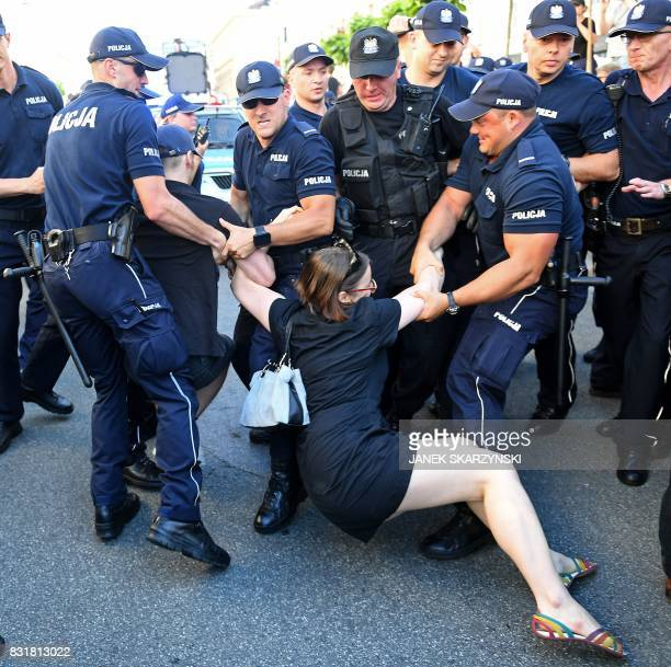 TOPSHOT Police officers remove a demonstrator who tried to block a farright extremists marching to celebrate the Polish Army Day marking the victory...